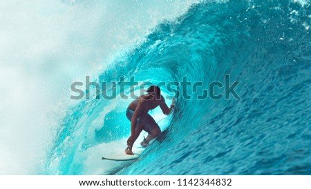 CLOSE UP: Exreme athlete surfs a big barrel ocean wave glistening in the summer sunshine. Spectacular tube wave splashes over the young surfer enjoying his active vacation in sunny French Polynesia. #1142344832