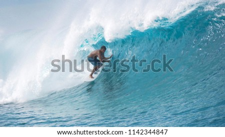Cheerful young surfer enjoying his cool summer vacation and surfing the big emerald waves in sunny French Polynesia. Spectacular shot of young surfboarder dragging his hands along the epic tube wave. #1142344847