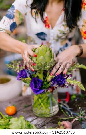 Close ups of woman florist's hands creating floral arrangements in garden #1142360735