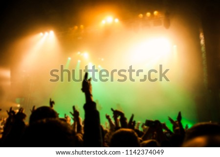 Musical concert. People in the concert hall at the disco . Singer in front of the audience. Fans at the concert. Blurred image / blurred photo.  #1142374049
