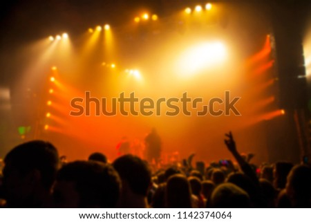 Musical concert. People in the concert hall at the disco . Singer in front of the audience. Fans at the concert. Blurred image / blurred photo.  #1142374064