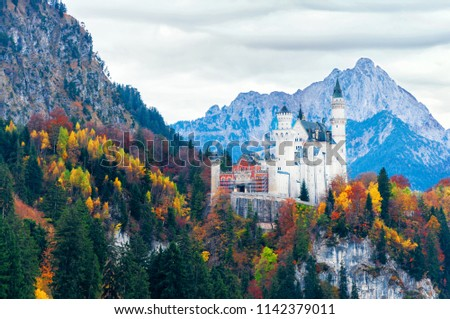 Scenic morning view of Neuschwanstein Castle with colorful autumn trees and the Alps on background. Bavaria, Germany. Beautiful autumn colorful scenery. #1142379011