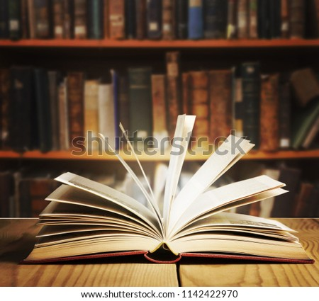 Old open book on a bookshelf background. #1142422970