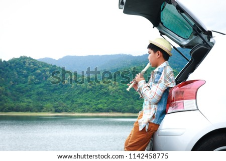 Small boy playing flute music behind the car In the midst of nature #1142458775