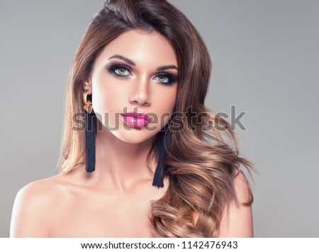 Beautiful hairstyle woman with brunette curly hair and beauty face over gray background female girl portraitgirl #1142476943
