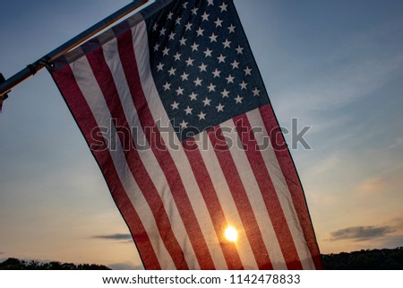 A beautiful patriotic picture of an American flag back-grounded by a summer sunset.