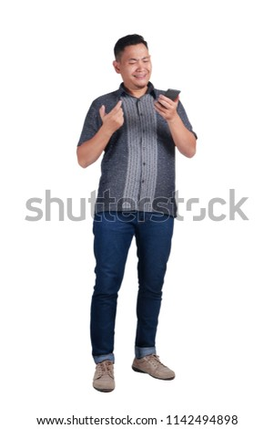 Young Asian man wearing blue jeans and batik shirt having bad news on phone, crying expression. Isolated on white. Full body portrait  #1142494898