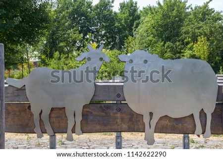 Silhouette of two sheep of metal