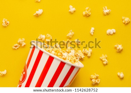 Popcorn salty lay shaking on yellow board #1142628752