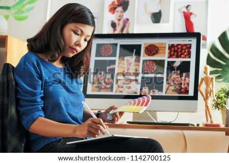 Young Vietnamese graphic designer choosing color scheme for her website