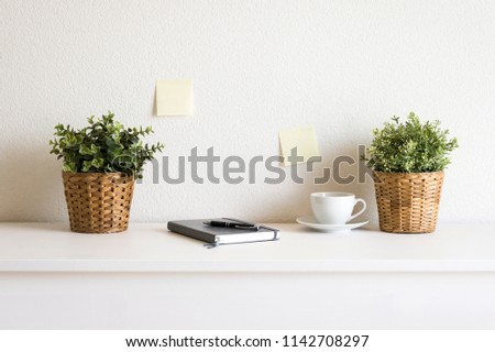 Sticky notes on wall, cup, plant and calendar on table in office #1142708297