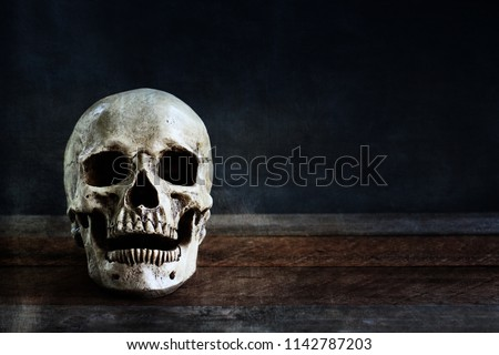 Halloween human skull on an old wooden table in front of black background with free space for text.