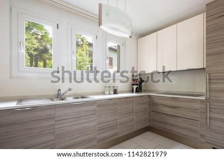 Modern kitchen with wood and a window where a lot of light enters. Nobody inside #1142821979