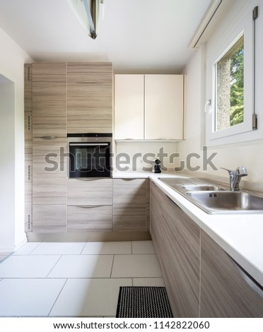 Modern kitchen with wood and a window where a lot of light enters. Nobody inside #1142822060