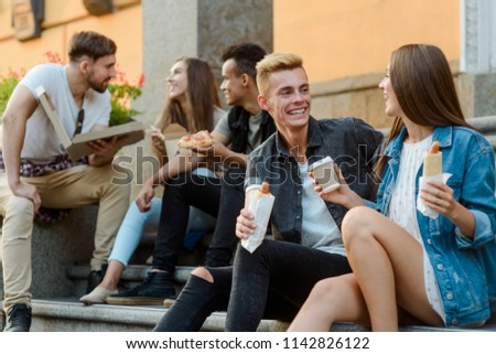 Students are talking and eating fast food during a break between classes, sitting on the porch of the college. #1142826122