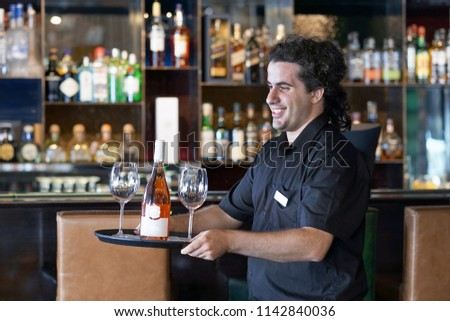A young men bartender carries a bottle of red wine with wine glasses on a tray to the client of the hote bar, restaurant.  The concept of service. #1142840036