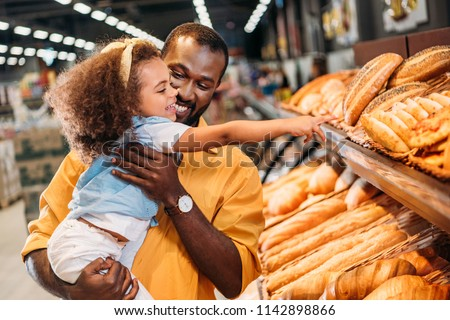 african american little child pointing by finger at pastry to father in supermarket  #1142898866