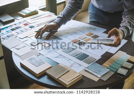 Architect designer Interior creative working hand drawing sketch plan blue print selection material color samples art tools Design Studio Royalty-Free Stock Photo #1142928158