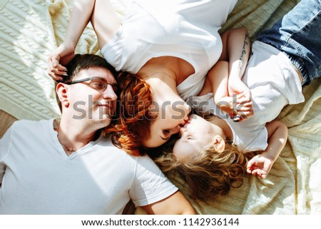 mother, father and a small daughter lie on the blanket. Top view #1142936144