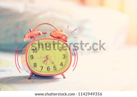 Alarm clock on desk near the window with morning light and copy space #1142949356