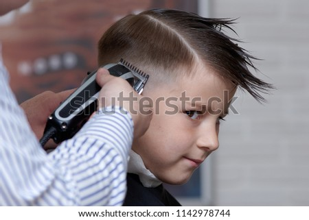 Barber making a haircut to a boy with cutting machine.  #1142978744