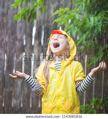 Happy girl with open mouth standing under the sprinkle on her yard #1143081836