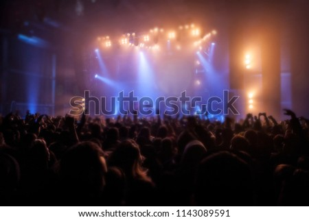 Musical concert. Music festival. People in the concert hall at the disco . Singer in front of the audience. Fans at the concert. Blurred image / blurred photo. #1143089591