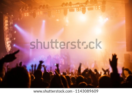 Musical concert. Music festival. People in the concert hall at the disco . Singer in front of the audience. Fans at the concert. Blurred image / blurred photo. #1143089609