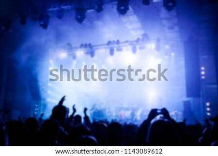 Musical concert. Music festival. People in the concert hall at the disco . Singer in front of the audience. Fans at the concert. Blurred image / blurred photo. #1143089612