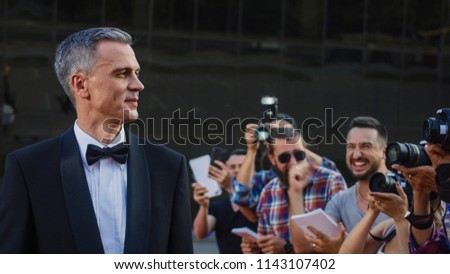Handsome adult man in tuxedo standing on red carpet of luxury event at photographers and fans