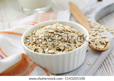 Oat flakes in a glass bowl and jug of milk for healthy breakfast #1143205100