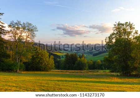Amazing, breathtaking panoramic view on the beautiful forest, alpine mountains and valleys and idyllic meadow fields of South Germany close to the Alpes with a blue sky before sunset #1143273170