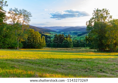 Amazing, breathtaking panoramic view on the beautiful forest, alpine mountains and valleys and idyllic meadow fields of South Germany close to the Alpes with a blue sky before sunset #1143273269