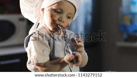 A funny kid eats a chocolate with the fork   in the kitchen. Portrait of a dirty boy in a culinary hat. #1143279152