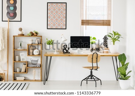 Large industrial desk with a computer by a window, a wooden bookcase and posters on a white wall in a stylish, scandi home office interior #1143336779