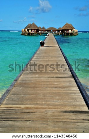 over water bungalows in turquoise lagoon on a luxury island on maldives #1143348458
