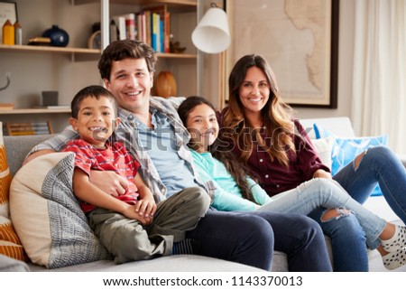 Portrait Of Happy Family Relaxing On Sofa At Home Together #1143370013