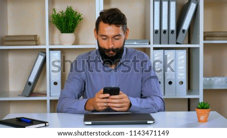 worker in start up company sitting in modern office using smart phone. young man with beard and mustache wearing blue shirt texting message or chatting online with friend. happy employer use mobile  #1143471149