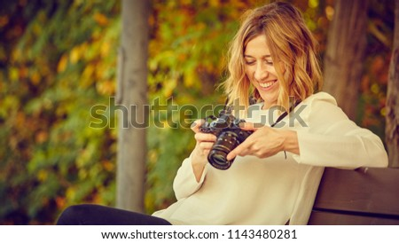 Photographer girl with mirrorless camera take photo in autumn