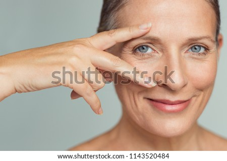 Portrait of smiling senior woman with perfect skin showing victory sign near eye on grey background.  Closeup face of mature woman showing successful results after anti-aging wrinkle treatment. #1143520484