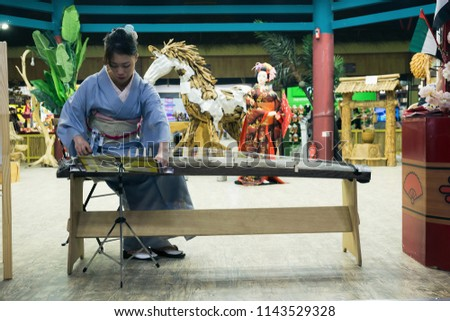 DUBAI, UAE - DECEMBER 4, 2017: Girl is playing a  traditional Japanese plucked instrument koto in the pavilion Japan of Global Village #1143529328
