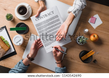cropped shot of businesspeople signing contract at workplace #1143542690
