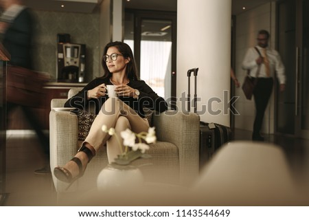 Businesswoman sitting at the airport lounge, waiting for the flight. Thoughtful woman sitting on sofa with coffee at airport waiting area. #1143544649