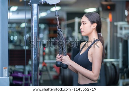 Young long black hair asian woman is working out at gym with black fitness dress #1143552719