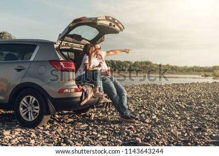 Happy Couple on Roadtrip into the Sunset in SUV Car #1143643244