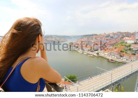 Young urban woman enjoying wind in her face when looking at Porto City, Portugal, Europe #1143706472