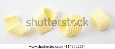 High Angle Panoramic Still Life View of Four Perfect Curls of Textured Butter on White Background #1143722354