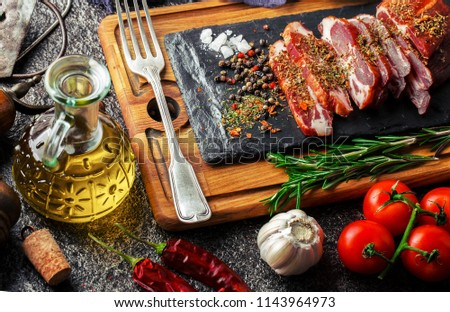 Raw meat on the kitchen table on a metallic background in a composition with cooking accessories #1143964973