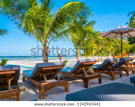 Umbrella and chair on the beach and sea ocean with blue sky around coconut palm tree for travel and vacation #1143965441