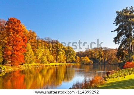 Autumn Landscape. Park in Autumn. The bright colors of autumn in the park by the lake. #114399292
